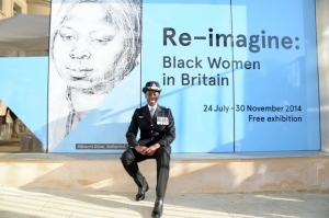 A black policewoman proudly sits in front of the sign for the BCA's Re-imagine Black Women exhibition